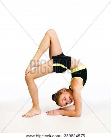 Flexible Cute Little Girl Child Gymnast Doing Acrobatic Exercise Isolated On A White Background. Spo