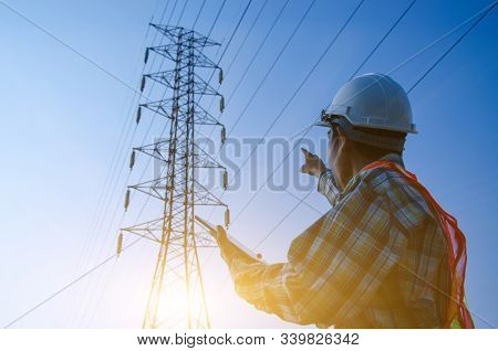 Electrical Engineer Holding And Using A Digital Tablet, Engineer Pointing At High Voltage Power Pylo