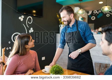 Mid Adult Waiter Serving Coffee To Female Customer At Restaurant