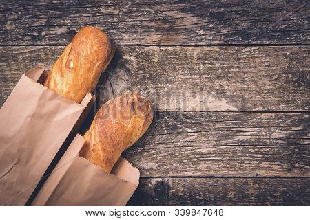 Fresh French Baguettes In Paper Bags On Wooden Background, Copy Space. Bread Shop. French Baguette O