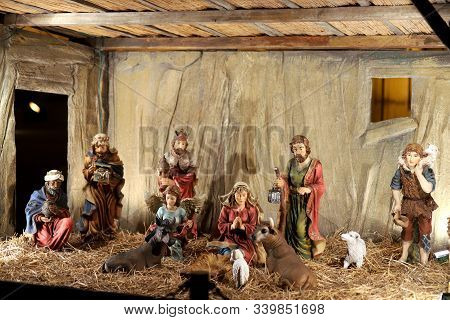 New Born Jesus Lying In Crib Or Manger In The Barn. Figurines Of Mary And Saint Joseph In The Stable