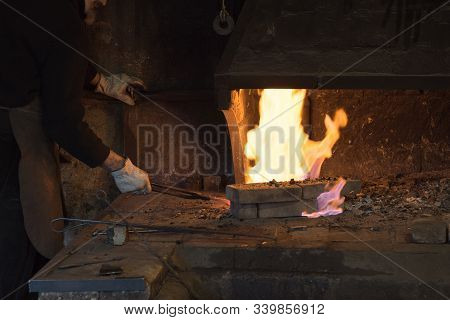 Ungersheim, Haut-rhin / France - 13. December, 2019: A Blacksmith Working Iron And Steel In An Old F