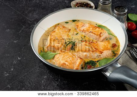 Close Up Of Salmon Steaks In Cream Sauce On Black Background