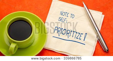 Note to self - prioritize. Handwriting on a napkin with a cup of coffee. Business, lifestyle and personal development concept.