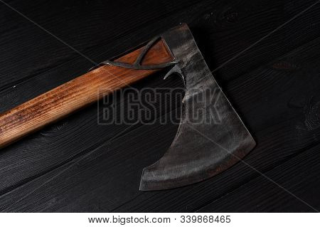 Real Scandinavian Ax On A Black Wooden Background, Still Life, Viking Ax, Burnished Steel