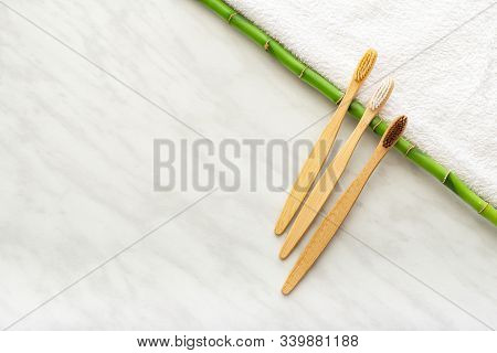 Bamboo Toothbrushes, Bamboo Plant On White Towel, Marble Background. Flat Lay. Natural Bath Products