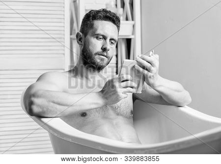Relaxed Guy Reading Book While Relaxing In Hot Bath. Relax At Home. Total Relaxation. Personal Hygie