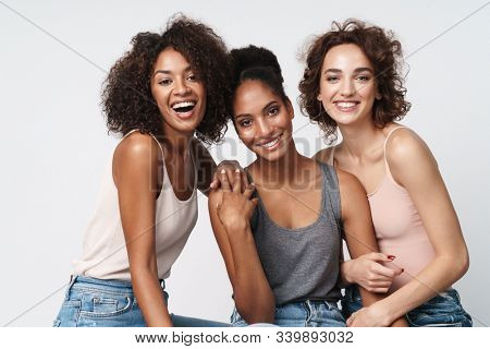 Portrait of three gorgeous multiracial women standing together and smiling at camera isolated over white background