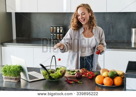 Happy young woman making a salad at the kitchen, chopping vegetables, looking at laptop computer, listening to music with earphones