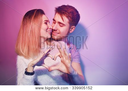 Close-up of beautiful couple kissing. Happy man and girl touching with their noses in pink backgroun