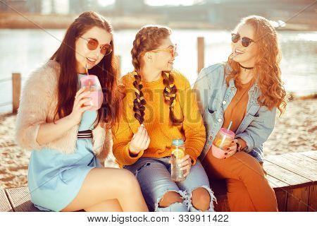 Three Girls Sit On The Beach , Near The River, Talk, Gossip, Joke, Laugh, Smile At Womans Day. Girls