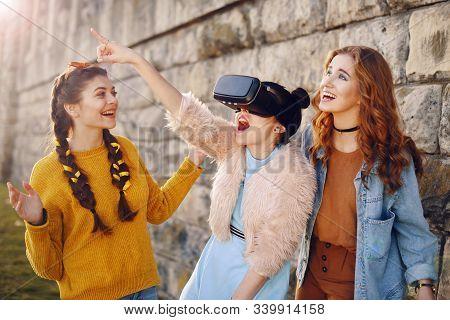Three Girls Near The River Against The Sky Having Fun. Fashion Girls In Sun Glasses. Jump, Rejoice,