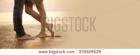A loving young couple hugging and kissing on the beach. Two lovers man and woman barefoot in the wet sand. Summer in love.