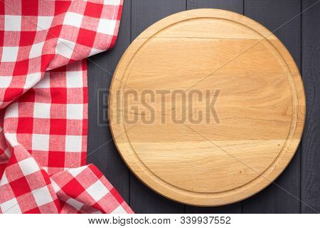pizza cutting board at rustic wooden plank board background, top view