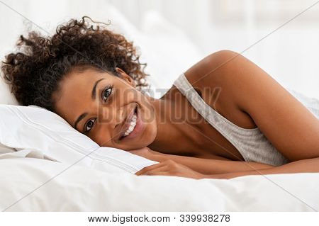 Young african woman looking at camera and smiling while lying on bed at home. Happy beautiful black girl wake up in the morning. Laughing fresh woman relaxing on bed.