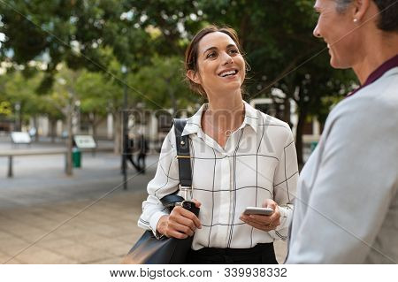 Happy business people in conversation at city street with copy space. Two mature businesswomen standing while talking about project. Successful corporate middle aged women discussing outside office.