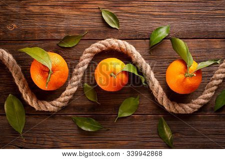 Ripe Tangerines And Rope On A Wooden Background. Abstract Composition With A Rope And Tangerines. Ta