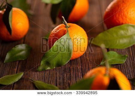 Tangerines With Green Leaves. Still Life Of Tangerines. Ripe Tangerines On A Wooden Table Close-up.