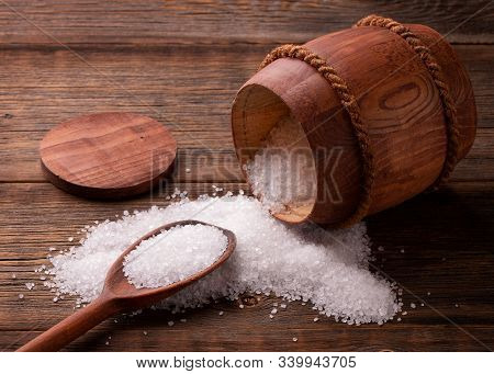 Salt Crystals Scattered On A Wooden Table. Sea Salt. Salt Poured From A Barrel. A Spoonful Of Salt.
