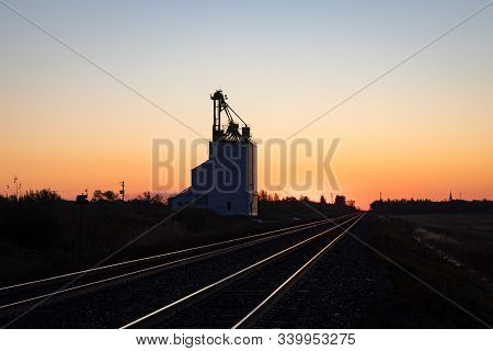 Grain Elevator Silhouetted Against Golden Prairie Sunrise