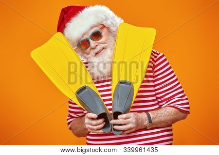 Jolly funny Santa Claus goes on vacation to the sea. Christmas Holidays, tourist trips to hot tropical countries. Bright yellow background. Copy space.