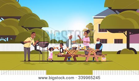 Multi Generation Family Preparing Hot Dogs On Grill African American Grandparents Parents And Childr