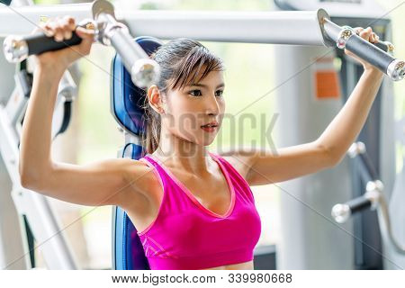 Sporty Asian Woman Exercising With Weightlift Machine At The Gym. Strong Female Determine With Her I