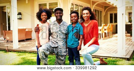 Portrait of a young adult African American male soldier in the garden outside his home, kneeling with his arms around his young son and daughter, his mixed race wife beside them, all smiling to camera