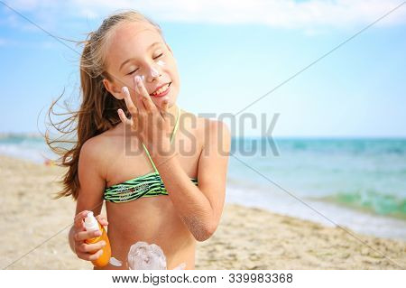 Girl Applying Protective Sunscreen On Face At Sea