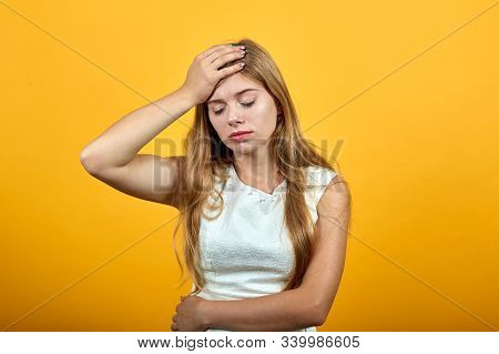 Attractive Blonde Young Woman Over Isolated Orange Background Wearing White Shirt Keeping Hand On He