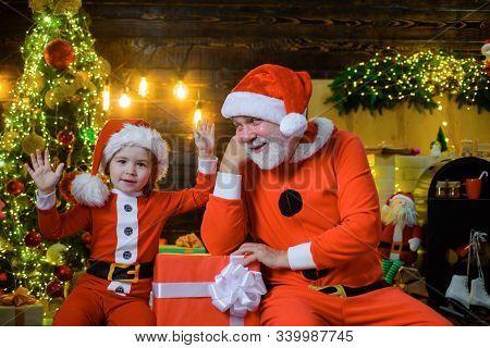 Merry Christmas. Happy Holidays. Santa Claus Man And Little Santa Boy At Home. Christmas Decoration.