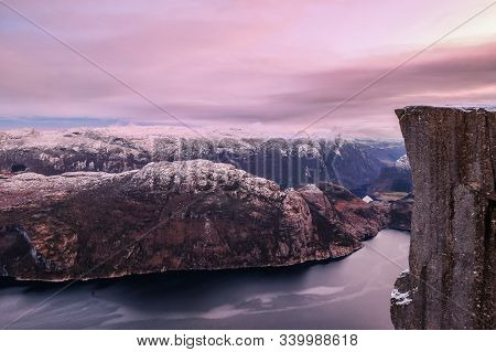 The Famous Preikestolen Pulpit Rock Over The Lysefjord, Some Snow On The Peaks And Beautiful Colors