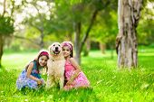 Two young girls hugging golden retriever dog in the park poster