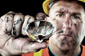 A dirty diamond miner covered in soot shows off a precious gem found in a coal mine. poster
