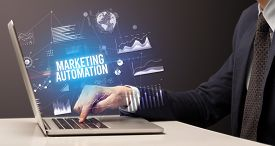 Businessman working on laptop with MARKETING AUTOMATION inscription, new business concept