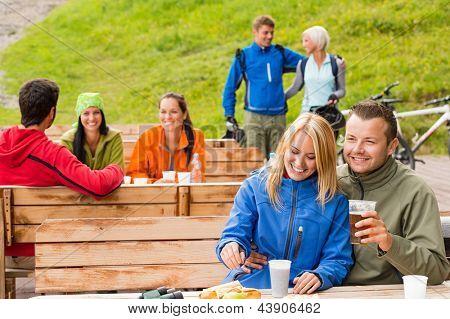 Cheerful people enjoying springtime weekend in rest area drinking beer