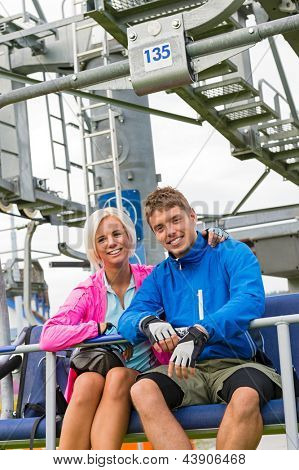 Smiling couple in sweatsuit sitting on char lift in springtime