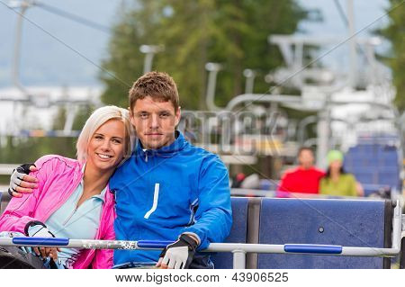 Hugging young couple in sweatsuits sitting on chair lift