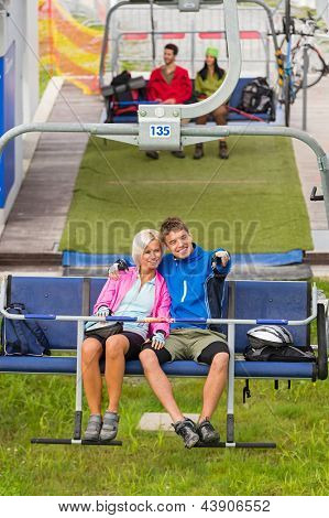 Cuddling couple pointing on chair lift in sweatsuits