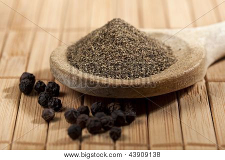 heap of powdered black pepper on a wooden spoon and pepper corns, shallow depth of field