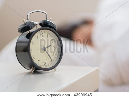 Alarm Clock In Front Of A Person Sleeping