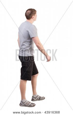 Back view walking handsome man. Sports-dressed young man moves. going guy. Rear view people collection. backside view person. Isolated over white. sports guy seeing what goes on the top of the goal
