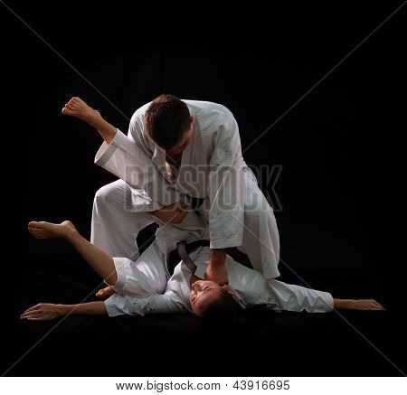 fighting karate couple, man and woman with black belts - champions of the world, on black background studio shot