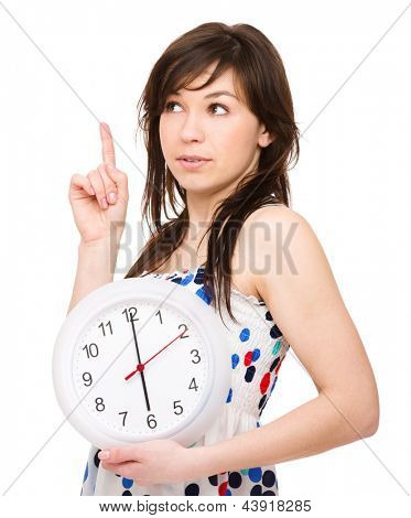 Young woman is holding big clock and pointing up, isolated over white