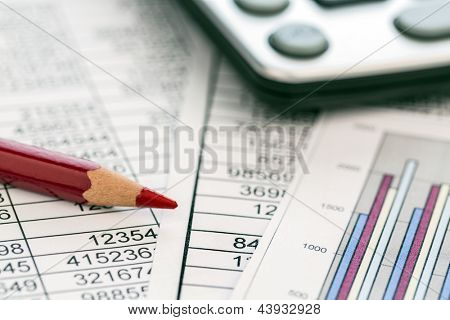 a calculator is on a balance sheet numbers are statistics. photo icon for sales, profit and cost.
