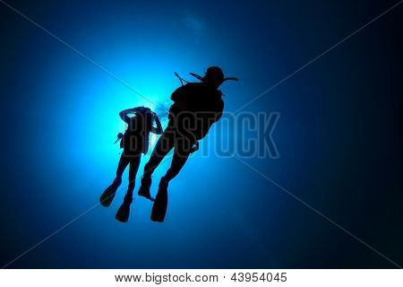 Two Scuba Divers underwater silhouettes against sun