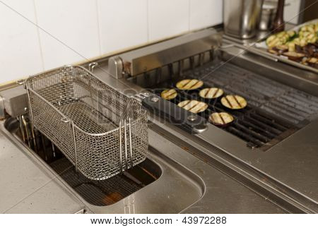 Deep fryer and grill on commercial kitchen in restaurant