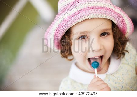 Young cute little girl tasting a lollypop