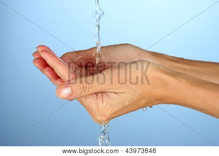 Washing hands on blue background close-up