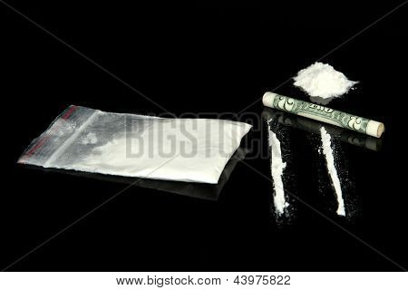 Cocaine drugs heap and lines with rolled banknote, close up